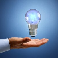 Businessman with illuminated light bulb concept for idea, innovation and inspiration